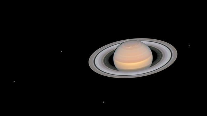 Esta imagen compuesta, captada por Hubble el 6 de junio de 2018, muestra a Saturno y sus anillos totalmente iluminados, junto con seis de sus 62 lunas conocidas. Las lunas visibles son (de izquierda a derecha) Dione, Encélado, Tetis, Jano, Epimeteo y Mimas. Image Credit: NASA/ESA/Hubble