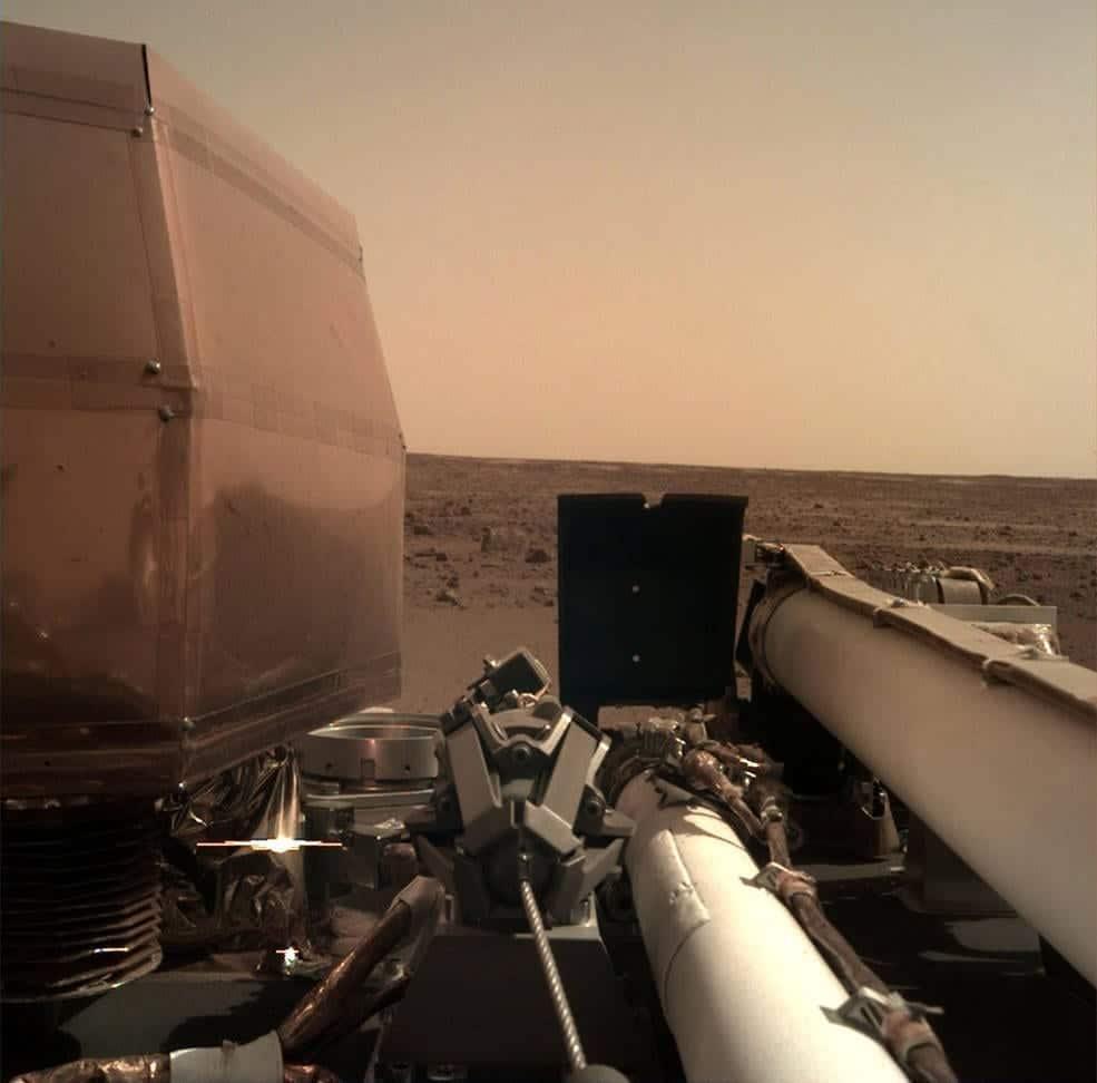 La Cámara de Implementación de Instrumentos (IDC), ubicada en el brazo robot de InSight, tomó esta fotografía de la superficie marciana el 26 de Noviembre de 2018, el mismo día en que la nave espacial aterrizó en el Planeta Rojo. La cubierta transparente para el polvo de la cámara aún está en esta imagen, para evitar que las partículas levantadas durante el aterrizaje se asienten en la lente de la cámara. Esta imagen fue transmitida desde InSight a la Tierra a través de la nave espacial Odyssey de la NASA, actualmente en órbita alrededor de Marte. Image Credit: NASA/JPL-Caltech