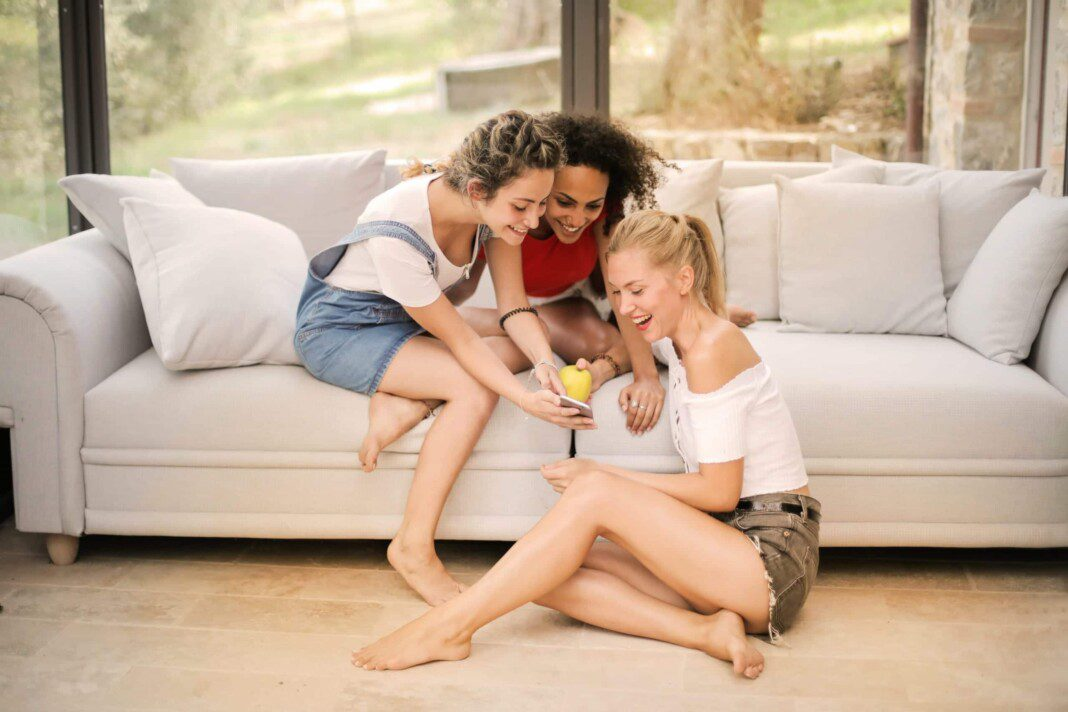 happy diverse friends laughing with smartphone at home 3764496 scaled
