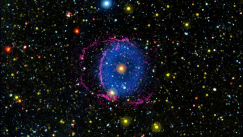 La Nebulosa del Anillo Azul consta de dos conos de gas en expansión expulsados al espacio por una fusión estelar. A medida que el gas se enfría, forma moléculas de hidrógeno que chocan con partículas en el espacio interestelar, provocando que irradien luz ultravioleta lejana. Invisible para el ojo humano, se muestra aquí como azul. Credits: NASA/JPL-Caltech/M. Seibert (Carnegie Institution for Science) / K. Hoadley (Caltech)/GALEX Team